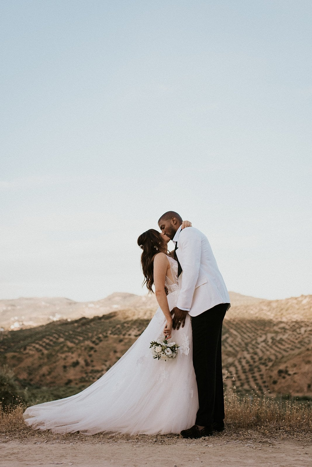 a couple kissing on their wedding day in spain