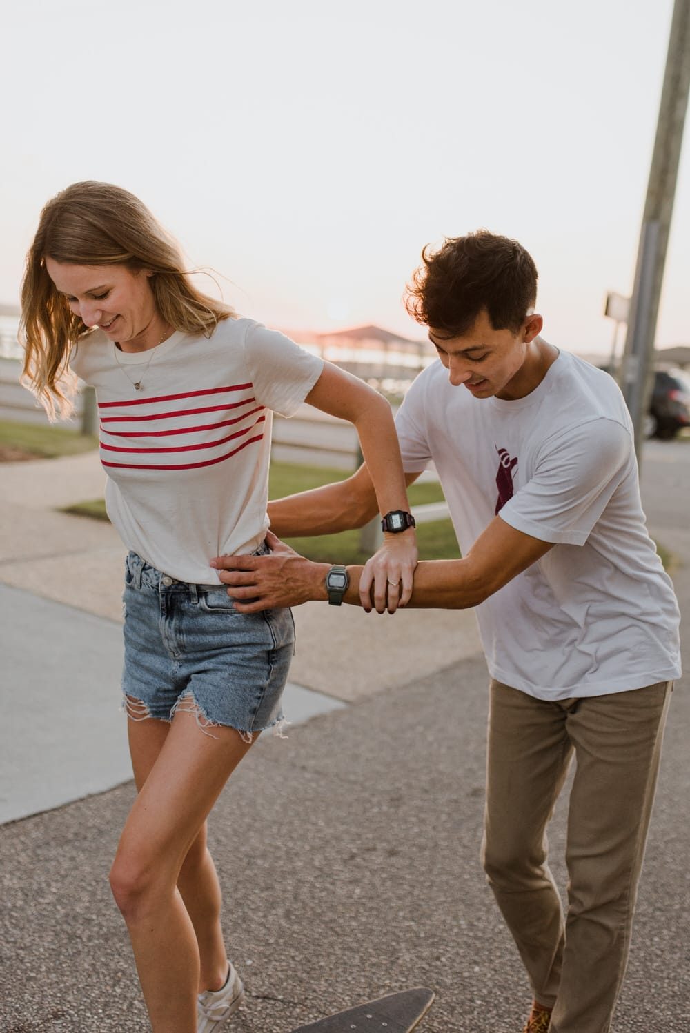 a boy helping a girl skate
