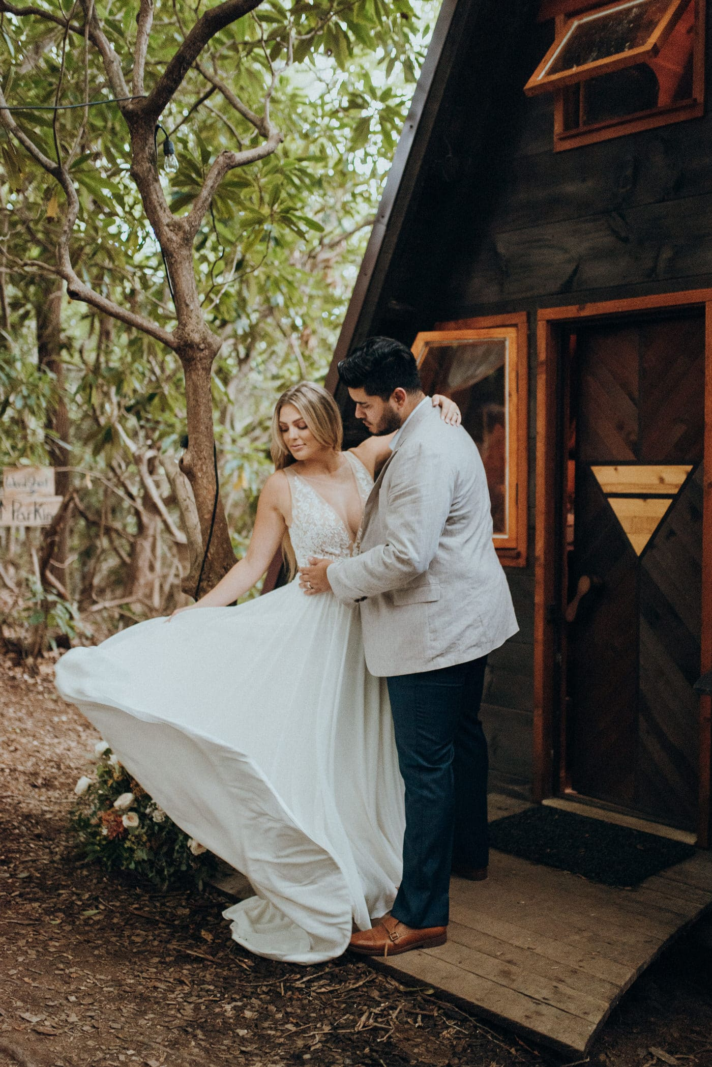 A bride and groom at a cabin in the woods